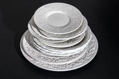 Sistema de placas de cerámica blancas hermosas del alivio de la cena en fondo negro imagenes de archivo
