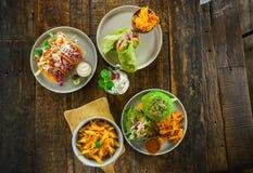 Sistema de platos vegetarianos en una opinión de sobremesa de madera Pastas, hamburguesa verde, falafel, shaurma Imagen de archivo