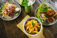 Sistema de platos vegetarianos en una opinión de sobremesa de madera Pastas, hamburguesa verde, falafel, shaurma, lavash del spir Fotografía de archivo