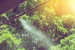 Sistema de rociadura del agua de la boca de la niebla en un día de verano caliente Imagen de archivo