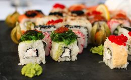 Sistema de rollos de sushi con vasabi y el jengibre en una placa oscura de la pizarra fotos de archivo libres de regalías