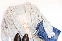 Sistema de ropa y de accesorios elegantes femeninos en la endecha blanca del plano del fondo, visión superior Fotos de archivo libres de regalías