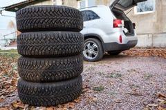 Sistema de ruedas y de neumáticos del invierno listos para cambiar cerca del coche, copyspace Fotos de archivo