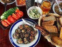 Sistema de setas, de tomate, de pepino y de cerveza fritos en una tabla de madera Imagen de archivo libre de regalías