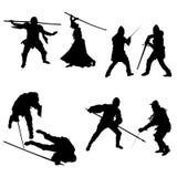 Sistema de siluetas de combatientes, de espadachines, de lanceros, de hombres y de mujeres en armadura con una espada, una lanza  Fotos de archivo libres de regalías