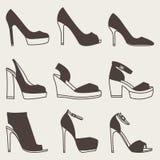 Sistema de siluetas marrones de los zapatos en fondo gris Fotos de archivo