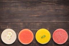 Sistema de smoothie y de jugo de la fruta en vidrios en fondo de madera Imágenes de archivo libres de regalías