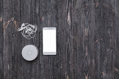 Sistema de sonido portante con los auriculares y la pantalla en blanco del teléfono móvil en la tabla de madera oscura Fotos de archivo