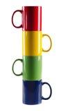 Sistema de tazas coloridas en un fondo blanco Foto de archivo libre de regalías