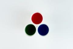 Sistema de tazas plásticas con las pinturas rojas, verdes y azules aisladas en gris Imagen de archivo libre de regalías