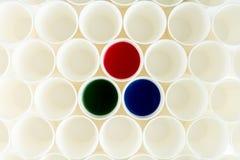 Sistema de tazas plásticas vacías y de tazas con las pinturas rojas, verdes y azules Imagenes de archivo