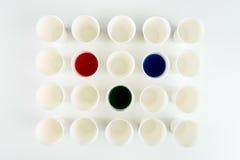 Sistema de tazas plásticas vacías y de tazas con las pinturas rojas, verdes y azules Foto de archivo libre de regalías