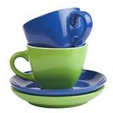 Sistema de tazas y de platillos verdes y azules, aislado en blanco. Imagenes de archivo