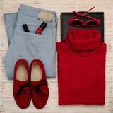 Sistema de tejanos, de suéter, de zapatos y de accesorios del color rojo o imagen de archivo