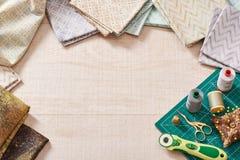 Sistema de telas en colores pastel y de herramientas de costura en la estera del arte Foto de archivo