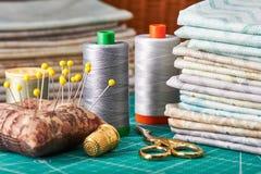 Sistema de telas en colores pastel y de herramientas de costura en la estera del arte Fotos de archivo
