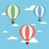 Sistema de tres globos coloridos del aire caliente de colores verdes y azules rojos con una cesta y las cuerdas que vuelan arriba Imágenes de archivo libres de regalías