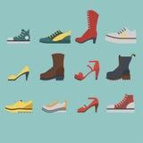 Sistema de zapatos del plano-estilo coloreados en fondo azul Hombres y zapatillas de deporte de las mujeres, zapatos y botas imágenes de archivo libres de regalías