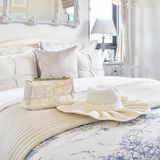 Sistema decorativo con el bolso del vintage, sombrero, libros en cama en dormitorio de lujo fotografía de archivo
