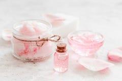 Sistema del balneario con las flores color de rosa extracto y cosmético para el cuerpo en el fondo blanco del escritorio Fotos de archivo libres de regalías