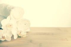 Sistema del balneario de la flor blanca de la orquídea y de la toalla rodada Fotos de archivo libres de regalías