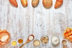 Sistema del bastidor del pan fresco y de los ingredientes en una tabla de madera Imagenes de archivo