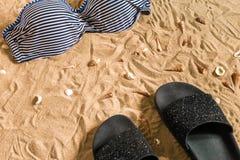 Sistema del bikini del verano y de la playa de los accesorios equipo del verano, del bikini elegantes de la playa y arena de mar  Imagenes de archivo