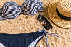 Sistema del bikini del verano y de la playa de los accesorios equipo del verano, del bikini elegantes de la playa y arena de mar  Imagen de archivo libre de regalías
