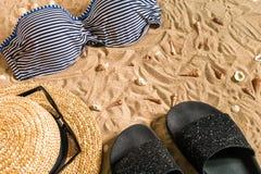 Sistema del bikini del verano y de la playa de los accesorios equipo del verano, del bikini elegantes de la playa y arena de mar  Imagen de archivo