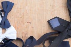 Sistema del bowtie y de la corbata de los accesorios del ` s del hombre en la tabla de madera Fotografía de archivo libre de regalías