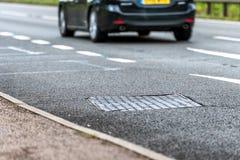 Sistema del colector del agua del drenaje en la autopista de Reino Unido con el coche en el movimiento rápido en fondo foto de archivo