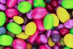 Sistema del diseño bajo festivo brillante de los chocolates de la formación de hielo del verde del amarillo del rosa de la gragea foto de archivo