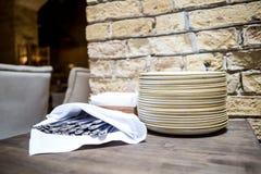 Sistema del dishware en la tabla en restaurante Pilas de placas blancas limpiadas para la comida fría de abastecimiento en sitio  Foto de archivo libre de regalías