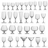 Sistema de cubiletes y de copas de vino de cristal vacíos Foto de archivo