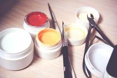 Sistema del esmalte de uñas y de manicura en fondo de madera oscuro Fotos de archivo libres de regalías