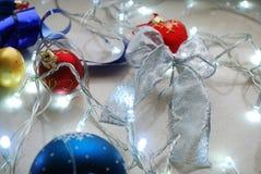 Sistema del extracto de la Navidad de ornamentos y de luces en fondo neutral Fotografía de archivo