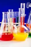 Sistema del laboratorio de química con los líquidos coloreados en una tabla sobre la parte posterior del azul Imagen de archivo