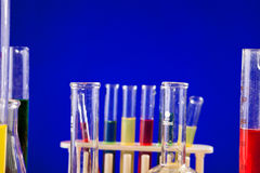 Sistema del laboratorio de química con los líquidos coloreados en una tabla sobre la parte posterior del azul Fotografía de archivo libre de regalías