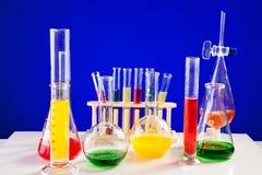 Sistema del laboratorio de química con los líquidos coloreados en una tabla sobre la parte posterior del azul Foto de archivo