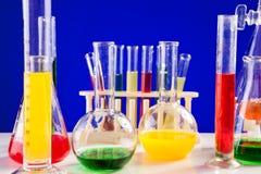Sistema del laboratorio de química con los líquidos coloreados en una tabla sobre la parte posterior del azul Fotos de archivo