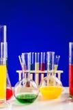Sistema del laboratorio de química con los líquidos coloreados en una tabla sobre la parte posterior del azul Fotos de archivo libres de regalías