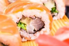Sistema del rollo de sushi cubierto en salmones Foto de archivo