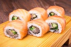 Sistema del rollo de sushi cubierto en salmones Imagenes de archivo