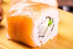 Sistema del rollo de sushi cubierto en salmones Imagen de archivo libre de regalías