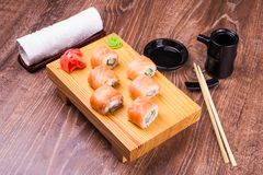 Sistema del rollo de sushi cubierto en salmones con el jengibre, la salsa de soja, la toalla y los palillos Fotos de archivo