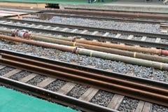 Sistema del tubo y de la válvula con los sensores y el cableado eléctrico entre las pistas de ferrocarril foto de archivo