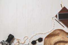 Sistema del viaje de la muchacha del inconformista: accesorios femeninos en la superficie planked blanco Fotos de archivo