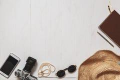 Sistema del viaje de la muchacha del inconformista: accesorios femeninos en la superficie planked blanco Fotografía de archivo libre de regalías
