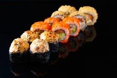Sistema delicioso de rollo de sushi con los pescados en un fondo negro con el menú de la reflexión y el concepto del restaurante imagen de archivo libre de regalías