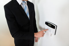 Sistema di allarme di Setting Home Security dell'uomo d'affari fotografia stock libera da diritti